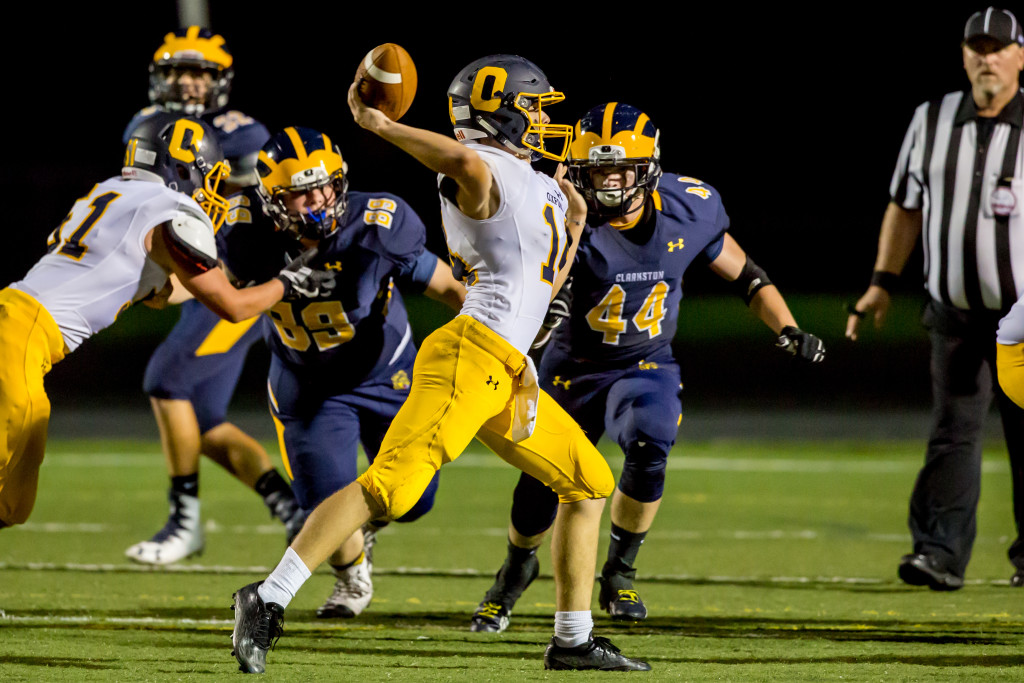 Oxford Quarterback Garrett Tyrell in mid-throw with Clarkston defenders coming at him. Photo by Larry Wright.