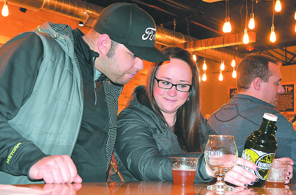 Oxford residents Curtis Caetano (left) and fiancee Abbey Moss check out the spoils of joining HomeGrown Brewing's Mug Club. Photo by C.J. Carnacchio.
