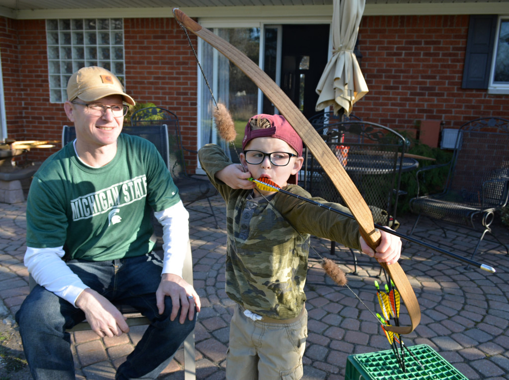 Carter Curtis, 5, a kindergartner at Daniel Axford Elementary, aims the longbow handcrafted by his father Aaron Curtis (left). Rocker Ted Nugent sent Carter a special message after seeing a video of him target shooting. Photo by  C.J. Carnacchio.