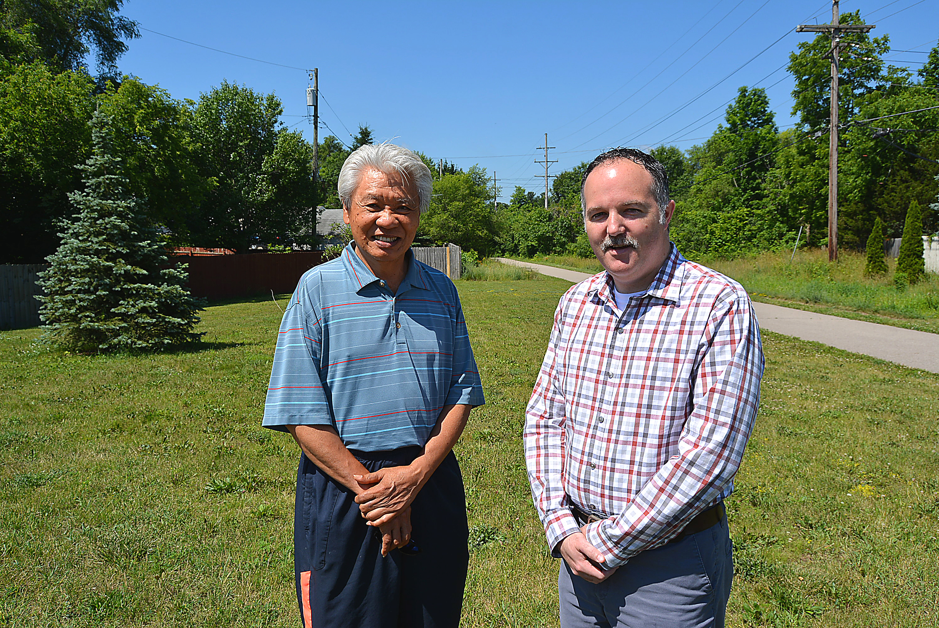 Dr. Joe Tunac (left), president of the Rotary Club of Oxford,  and Bryan Cloutier, the incoming club president, stand  on the vacant village land they wish to transform into a public park. Photo by C.J. Carnacchio.