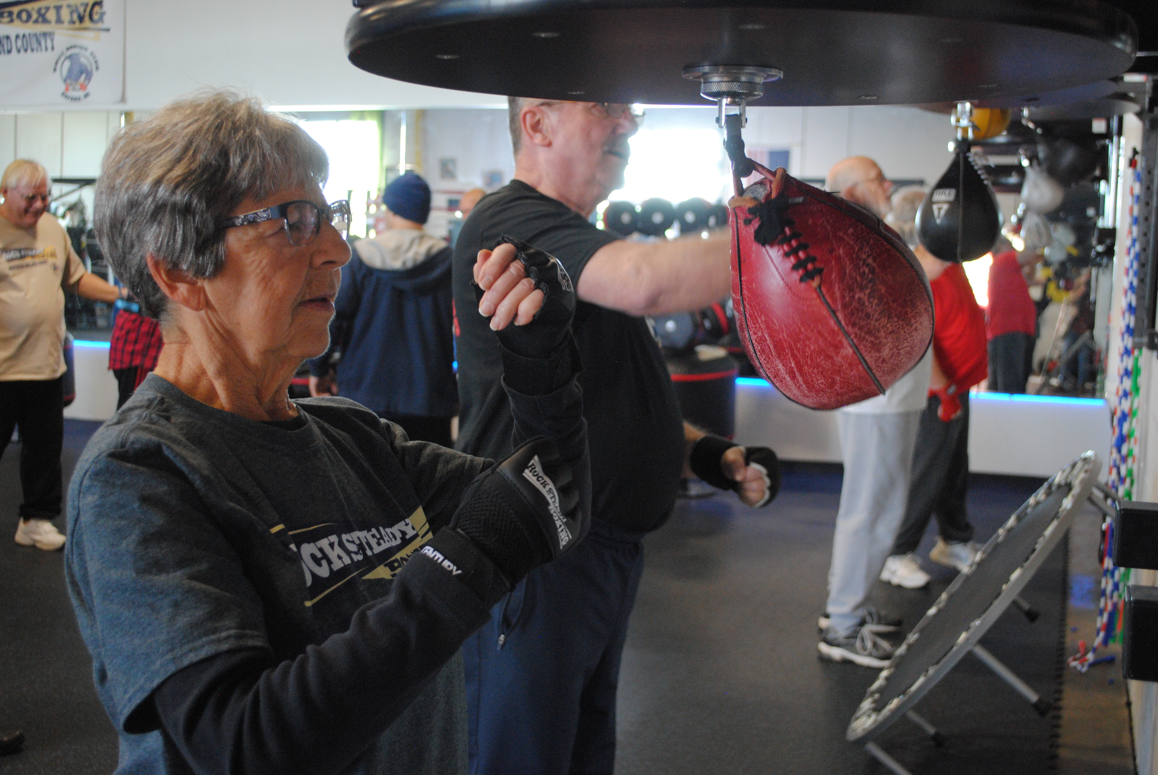 Lois Dockham takes on a speed bag during a Rock Steady class. She might be smaller than her classmates, but she has the speed bag pounding the wall just like the rest. Photo by Shelby Tankersley.