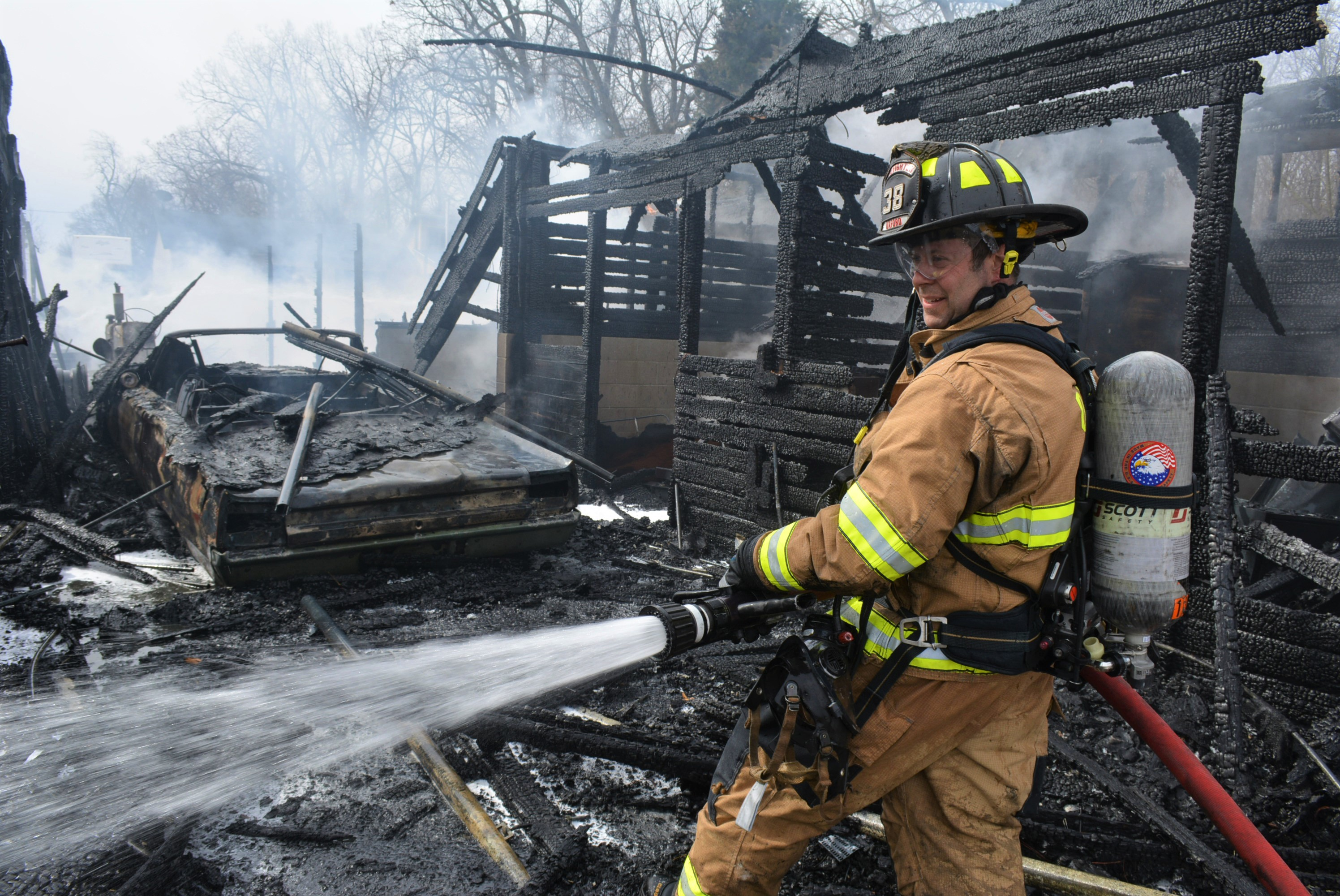 Back in March, OXFD tried to save the Wilson family's barn. Pictured is firefighter Randy Darnell hosing down the barn's remains. Photo by C.J. Carnacchio.