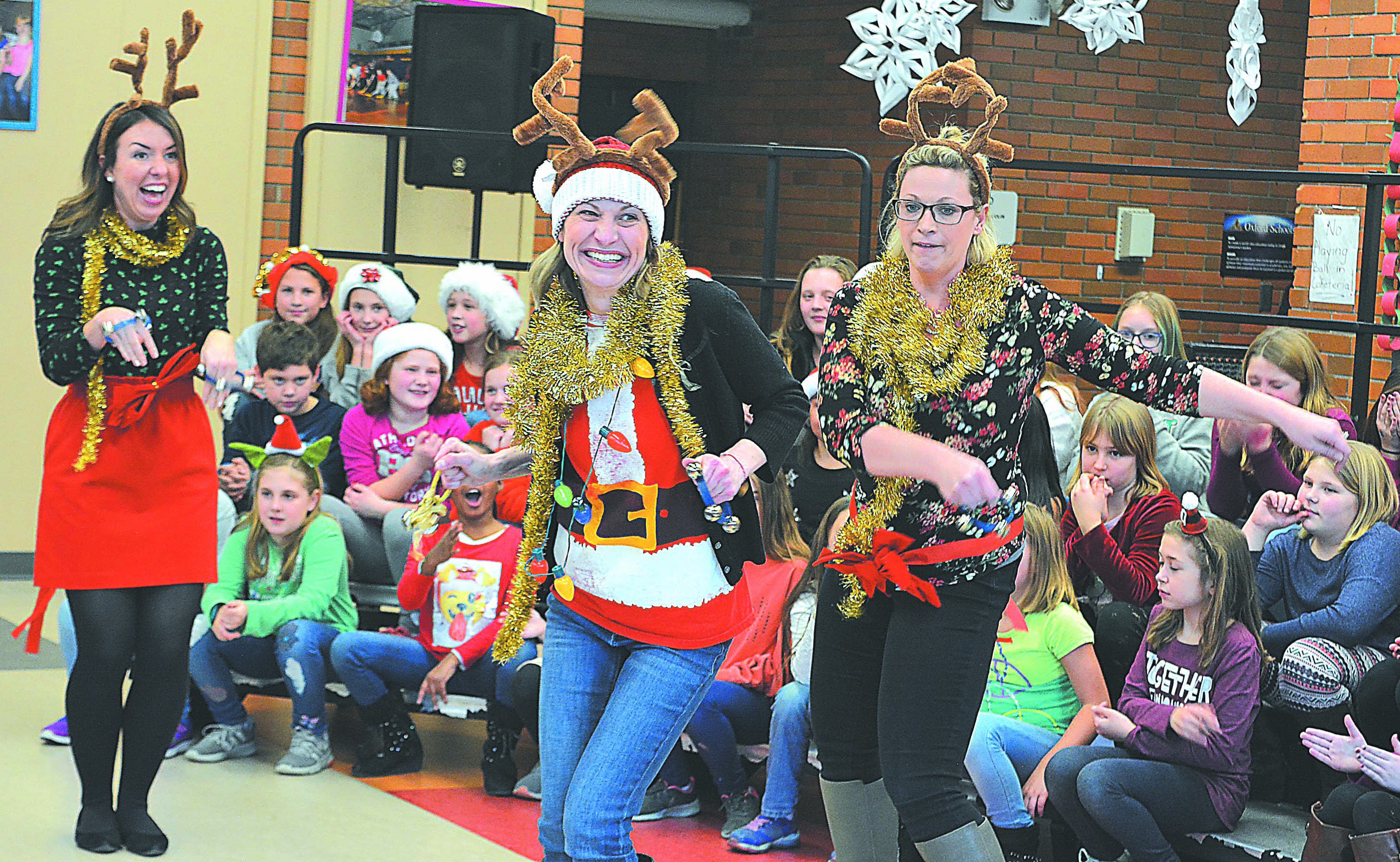 Teachers Alicia Daniels (from left), Jillian Jesmore and Rachel Hart show off their dance moves as reindeer who like to boogie down. Photo by C.J. Carnacchio.