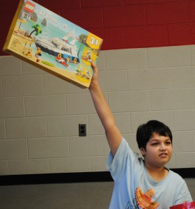 Salvador, a 12-year-old, held his new LEGO set high in the air, showing off his new toy to his buddies. Photo by Shelby Tankersley.