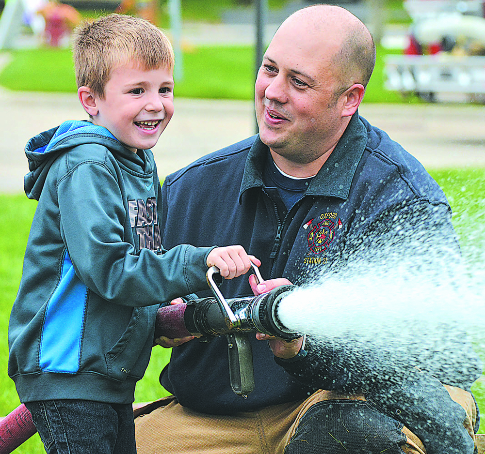 Daniel Axford Elementary kindergartner Alex Ballard, 5, learns to aim a fire hose with help from Oxford firefighter Brian Phillips. This is just one of many photos from the Oxford Fire Department open house held in October. Photo by C.J. Carnacchio.