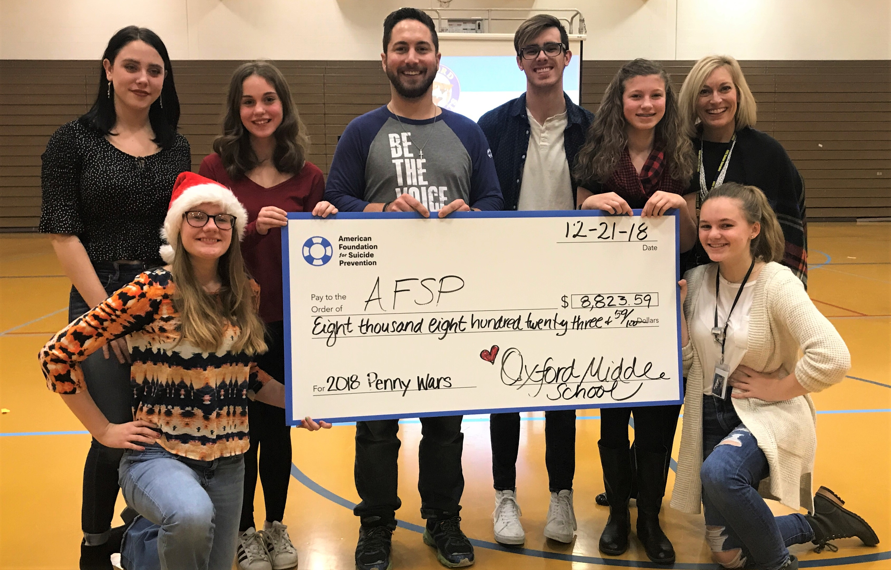 Posing with the $8,800 check is Ava Gordon (front, from left) and Aubrey Greenfield. In the back is OHS graduate Riley Juntti (from left), Allison Ried, AFSP representative Steve Windom, OHS graduate Dylan Koss, Taylor Reid, Allison Reid and OMS Principal Dacia Beazley. Photo provided.